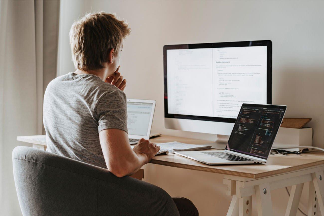 Junger Mann entwirft Website am Computer